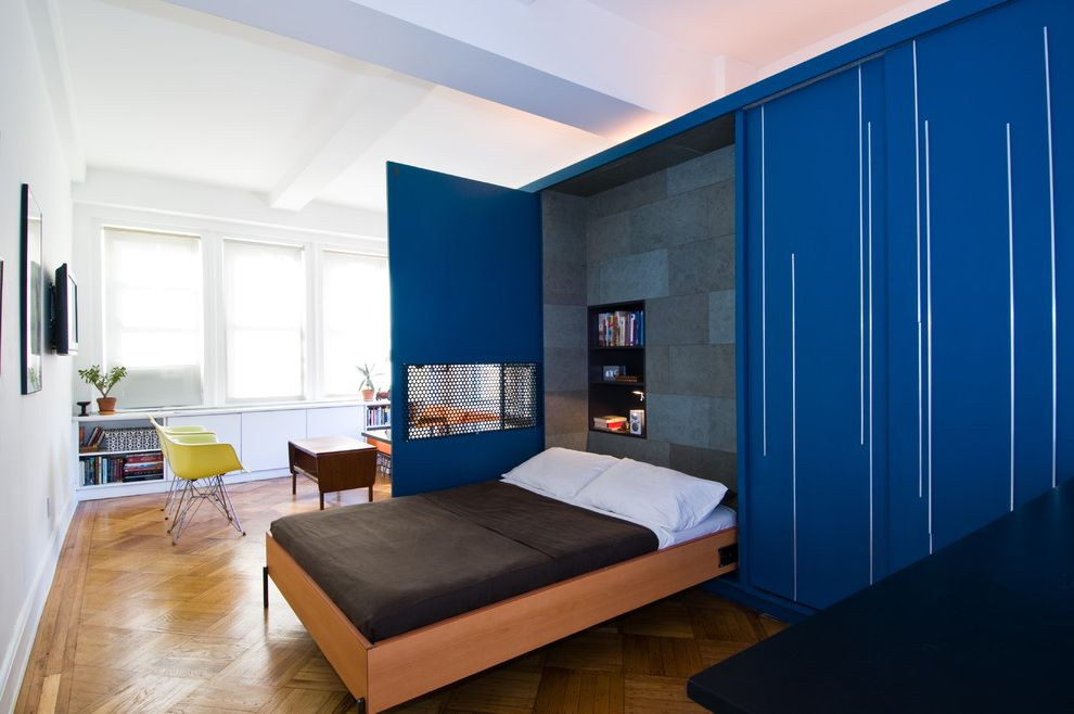 Bed That Comes Out of the Wall   Contemporary Bedroom Also Blue Casters Coffee Table Custom Cabinetry Day Bed Folding Panels Metal Screen Murphy Bed Orange Sofa Parquet Floor Privacy Seating Area Sleeping Area Small Wood Stool Studio Apartment Work Area
