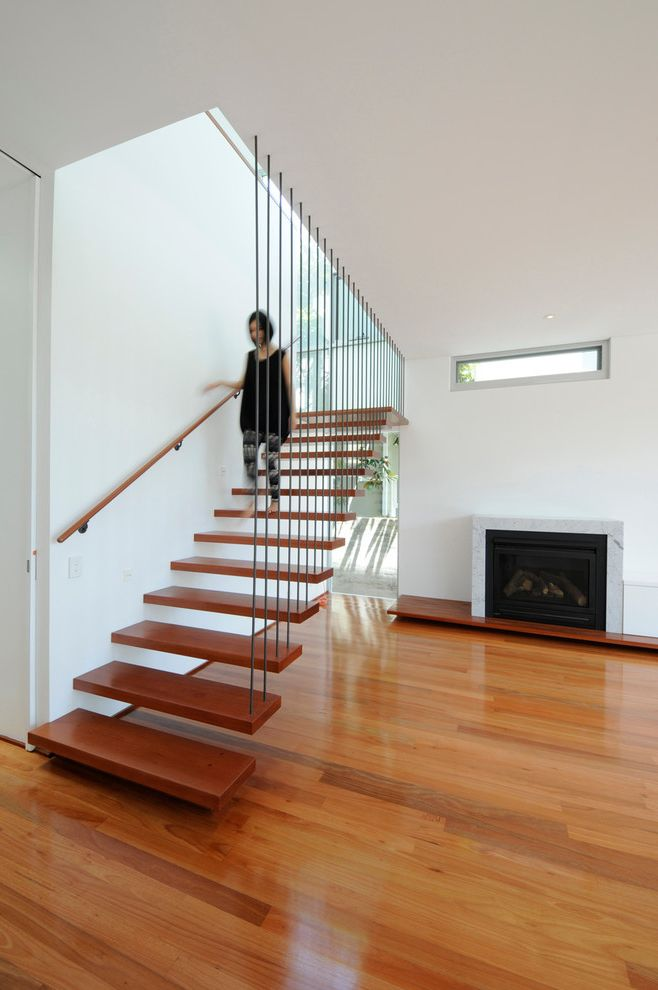 Floating Stairs Cost with Modern Staircase Also Cable Guardrail Cantilevered Stairs Family Room Fireplace Floating Stairs Living Room Open Rises Staircase Straight Run Staircase Timber Floor Wood Flooring Wood Staircase