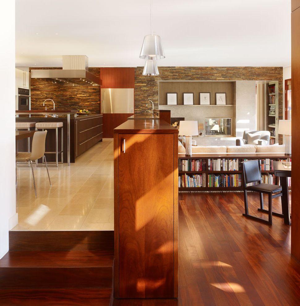 Floor Level Sofa with Modern Living Room  and Bookcase Built in Bookshelf Dark Wood Kitchen Mid Century Open Space Pendant Light Stone Wall Tiled Floor Veneer Wood Floor