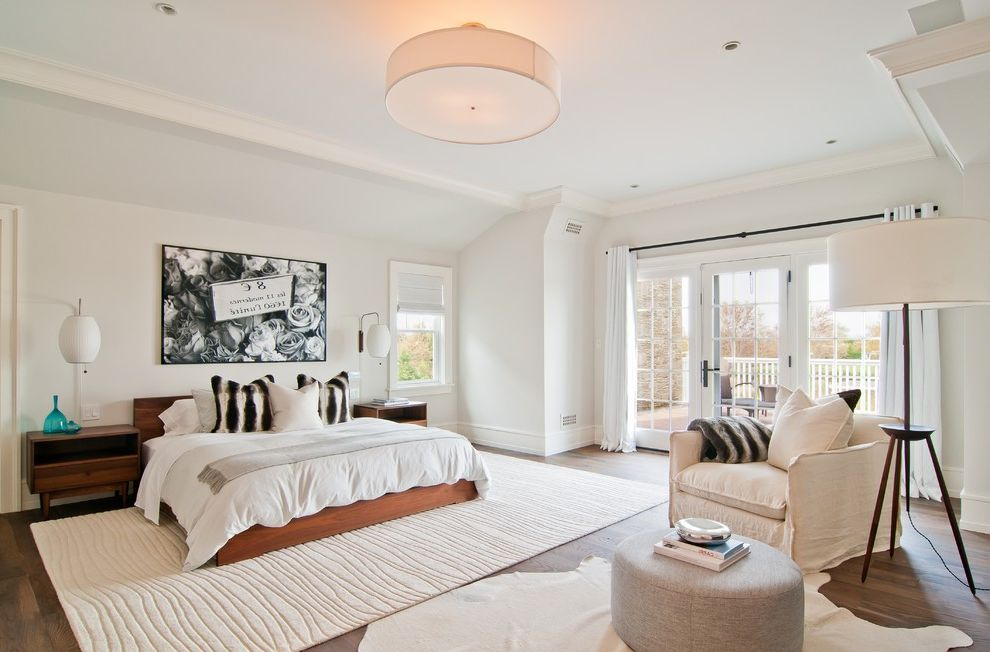 Gold and White Rug   Transitional Bedroom Also Glass Door Gray Armchair Gray Ottoman Slipcovered Chair White Animal Rug White Bedding White Curtains White Molding White Rug White Trim White Wall Wood Bed Wood Nightstand