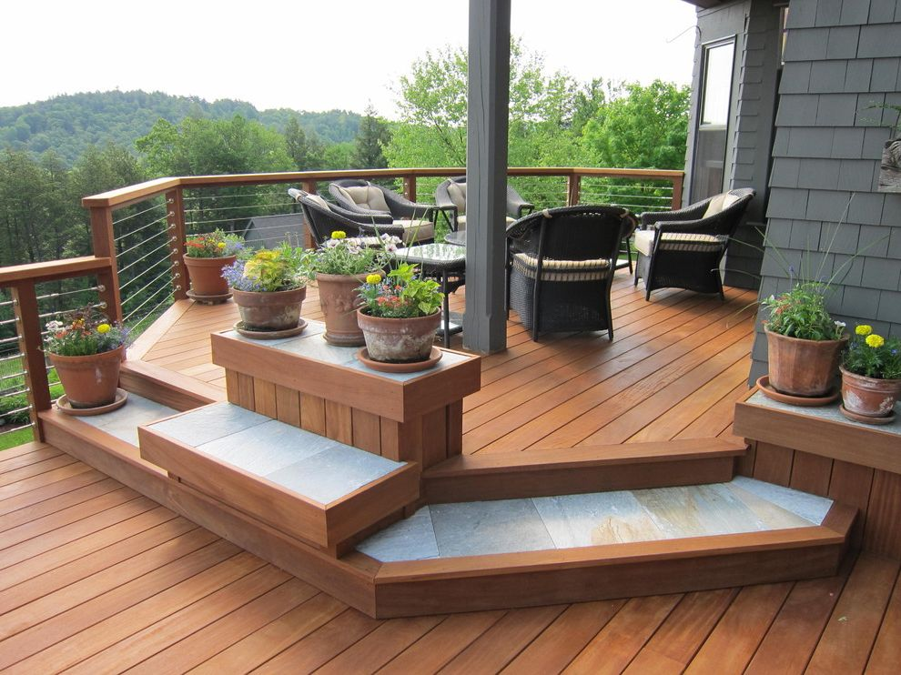 How Much to Build a Deck with Traditional Porch  and Cable Railing Circular Porch Flower Pots Gray Exterior Gray Siding Outdoor Furniture Outdoor Seating Porch Railing Potted Plants Rail Posts Stone Accents Stone Inlay Wood Patio Wood Porch