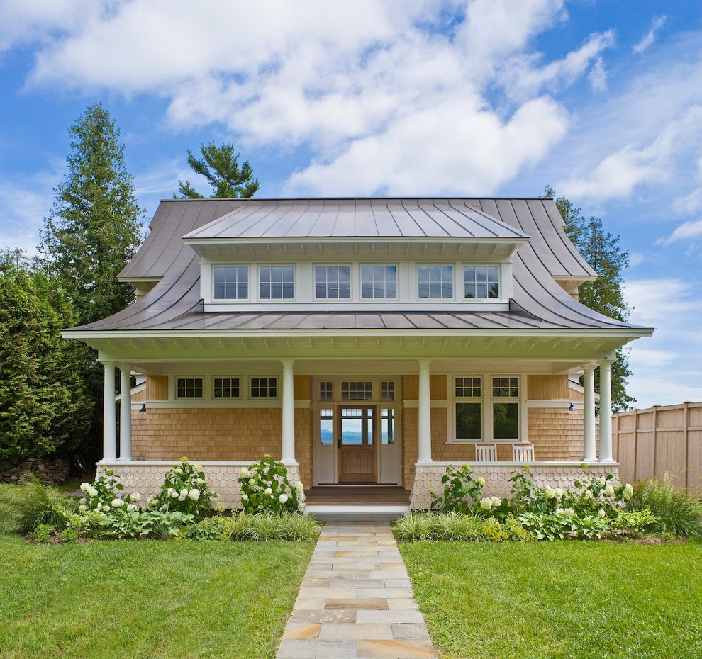 Metal Roof vs Shingles with Beach Style Exterior Also Awning Windows Cedar Shakes Dormer Entry Hydrangea Landscape Lawn Metal Roof Muntins Path Patio Rocking Chairs Shingles Slate Steps Tapered Columns Transom Windows Walkway White Trim Wood Fence