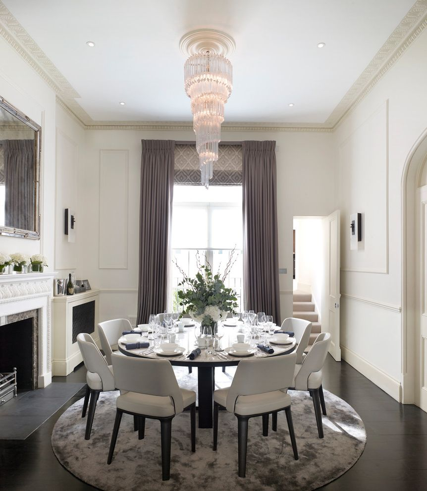 Raymour and Flanigan Near Me with Traditional Dining Room  and Ceiling Detail Chandelier Chandeliers Circular Rug Circular Table Crown Molding Curtains Dining Room Tall Windows Victorian Fireplace Wainscoting White Dining Chairs
