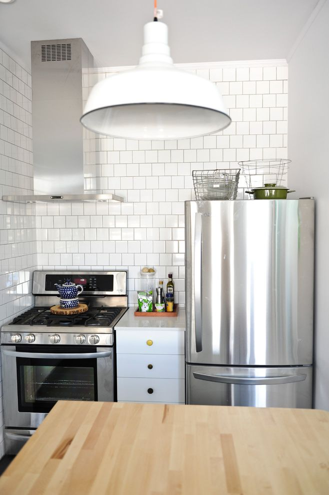 Samsung Stoves with Eclectic Kitchen Also Butcher Block Ceiling Light Funky Knobs Gray Grout Kitchen Island Oven Hood Small Kitchen Square Tiles Stainless Steel Stainless Steel Vent Tiled Wall White Counter White Tile Wire Baskets