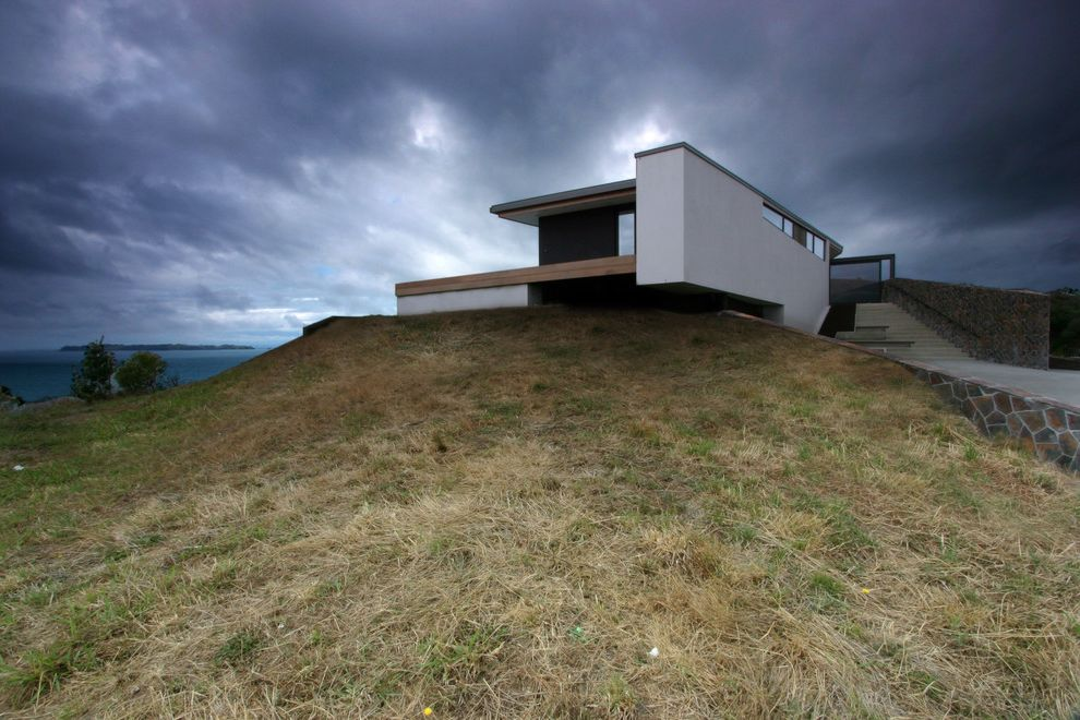 What is a Berm with Modern Exterior  and Angles Cantilevered Eaves Flagstone Grasses Hillside Low Stone Wall Natural Landscape Ocean View Steps Stucco