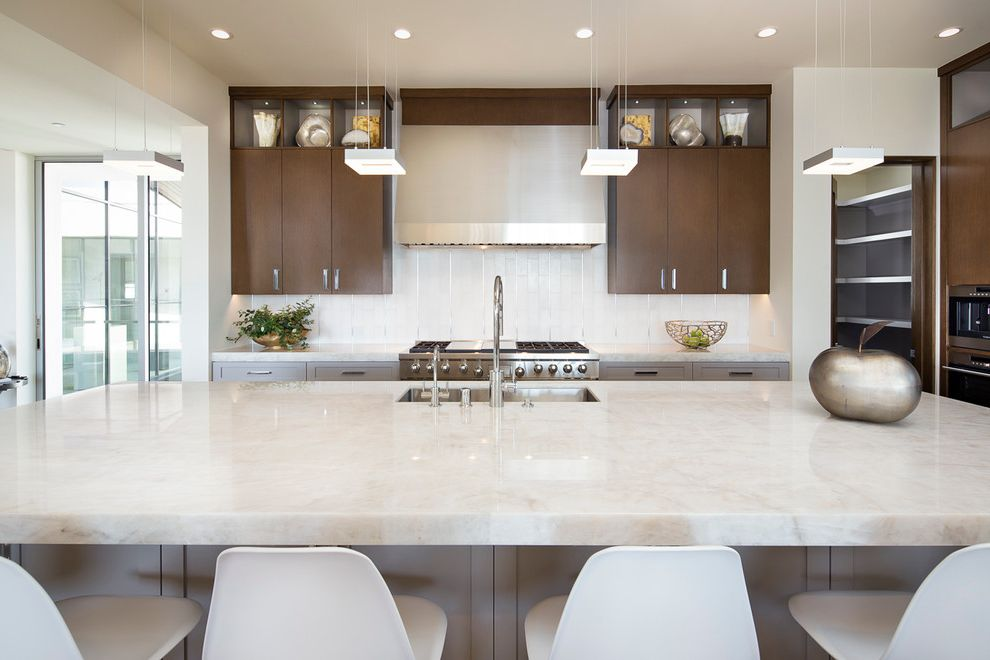 What is Quartzite with Contemporary Kitchen Also Clean Lines Glam Pendant Lights Over Island Quartzite Counters Rift Oak Cabinetry White Counter Stools