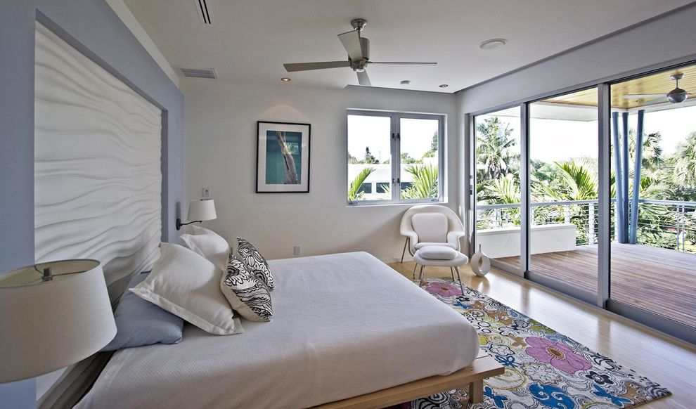 Bright Floral Rug with Modern Bedroom Also Accent Wall Blue Wall Ceiling Fan Floral Area Rug Light Wood Floor Master Bedroom Patio Sliding Glass Door Wall Light White Bedding White Ceiling White Lounge Table White Ottoman White Throw Pillow White Wall
