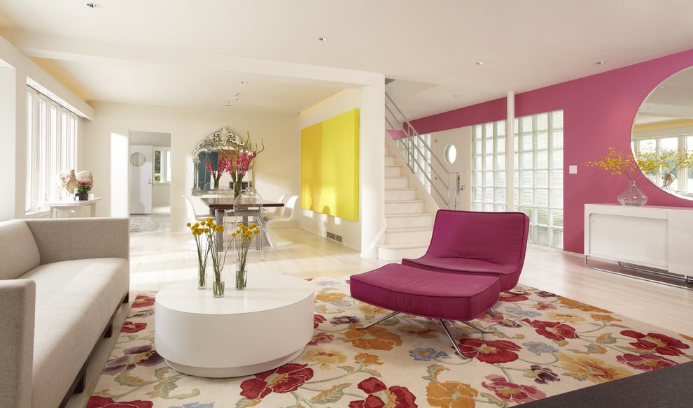 Bright Floral Rug with Modern Living Room  and Artwork Coffee Table Dining Area Floral Area Rug Glass Block Lounge Chair Metal Railing Pink Round Mirror Seating Area Sofa Staircase White Stained Wood Floors White Walls Yellow