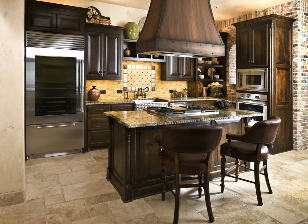 Cisco Flooring Supplies with Rustic Kitchen  and Brick Wall Dark Stained Wood Glass Front Refrigerator Hood Over Island Leather Counter Stools Raised Panel Woodwork Rustic Stainless Steel Appliances Tile Backsplash Tile Floor Travertine