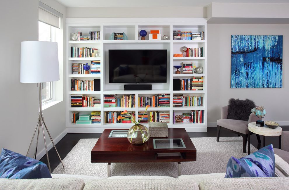 Clean House Tv Show   Contemporary Family Room  and Area Rug Artwork Baseboards Bookcase Bookshelves Built in Shelves Colorful Books Dark Floor Gray Walls Neutral Tones Roller Blinds Tripod Lamp Urban Wall Mount Tv Wood Coffee Table