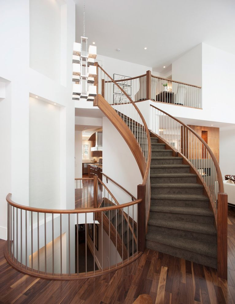 Dalworth Carpet Cleaning   Contemporary Staircase  and Carpeted Stairs Chandelier Curved Banister Niche Recessed Lights Spiral Walnut Staircase Stairwell Vaulted Ceiling Walnut Flooring White Walls Wood Gain Wood Handrail