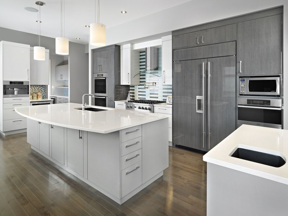Derr Flooring with Contemporary Kitchen  and Flush Cabinets Gray Island Gray Stained Wood Floor Hood Integrated Kitchen Pendant Lights Stainless Steel Appliances Tile Backsplash White Counters
