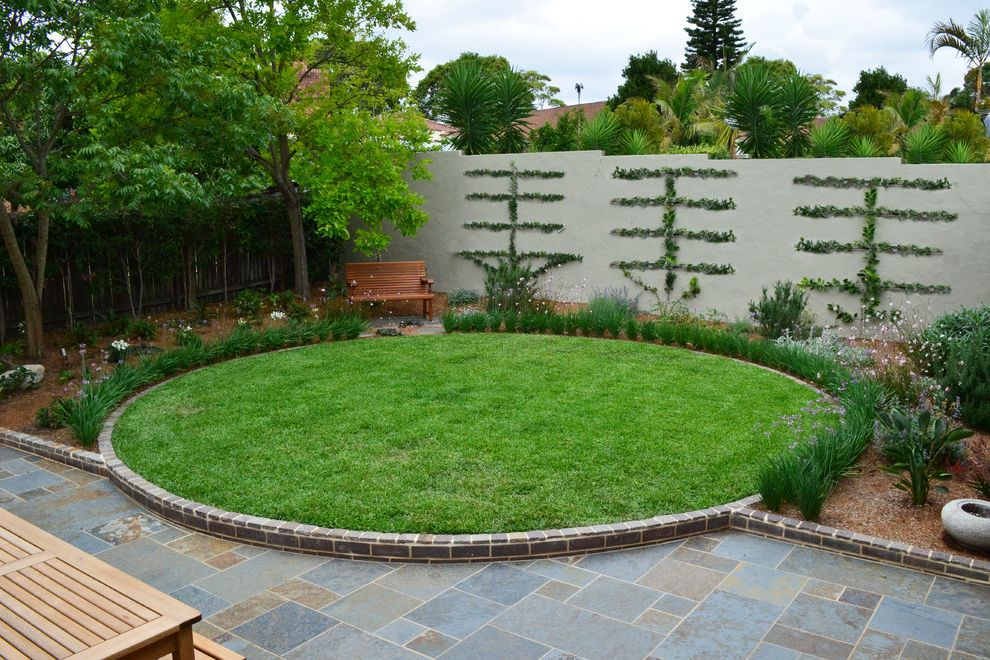 Down to Earth Lawn Care with Contemporary Landscape Also Bushes Garden Wall Grass Lawn Living Wall Mulch Purple Flowers Round Lawn Shrubs Stone Patio Stone Trim Stucco Wall Trees White Flowers Wood Bench Wood Fence