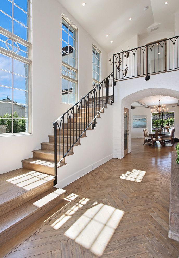 Herringbone Wood Floor with Beach Style Entry  and Herringbone Floor High Ceiling Metal Railing Tall Windows Vaulted Ceiling