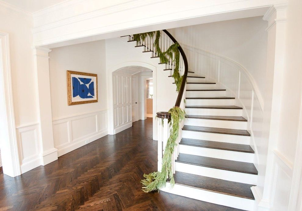 Herringbone Wood Floor with Traditional Staircase  and Artwork Chevron Christmas Decorations Curved Staircase Dark Floor Garland Parquet Floor Wainscoting Wall Art Wall Decor White Wood Wood Flooring Wood Molding