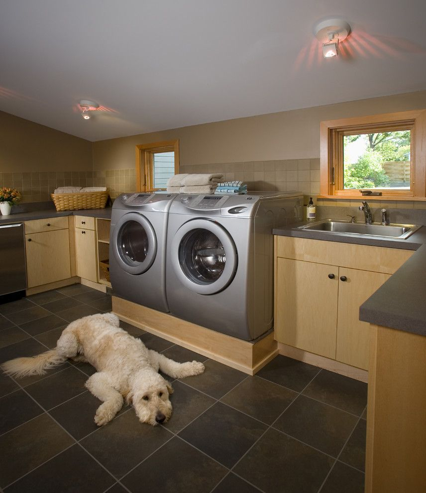 Lg Washer Dryer Pedestal with Contemporary Laundry Room Also Dark Flooring Dog Light Wood Cabinets Low Ceiling Platform Sloped Ceiling Stainless Sink Storage Tan Walls Tile Backsplash Tile Floor Washer Dryer Wood Framed Windows