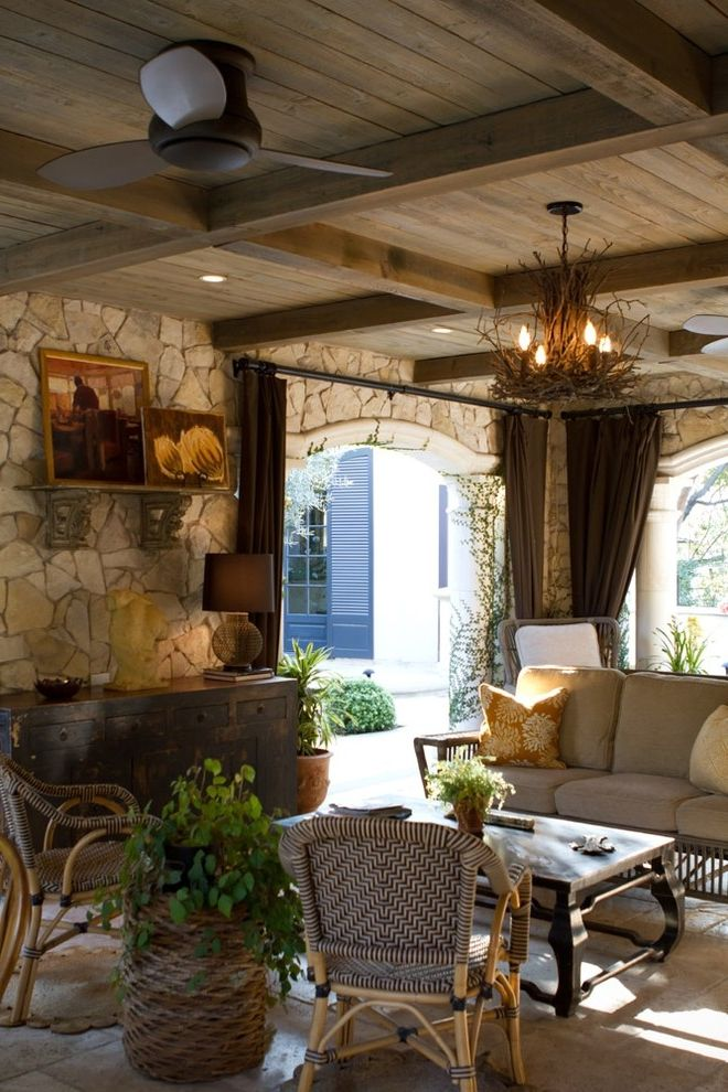 Lowes Bloomington in with Rustic Patio  and Cane Chairs Ceiling Fan Chandelier Credenza Curtain Panels Outdoor Curtains Rustic Stone Walls Tile Floor Travertine Floors Wicker Basket Wicker Sofa Wood Ceiling Woven Chairs