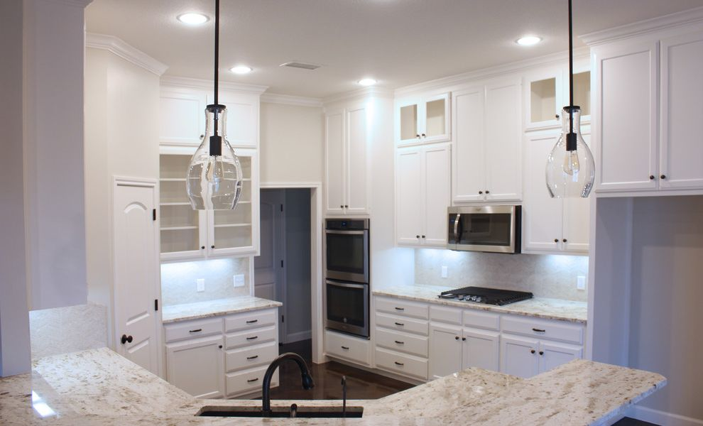 Mark Payne Homes with Traditional Kitchen  and Custom Cabinets Globe Pendant Light Oil Rubbed Bronze Painted Cabinets Stained Concrete Stainless Steel Appliances