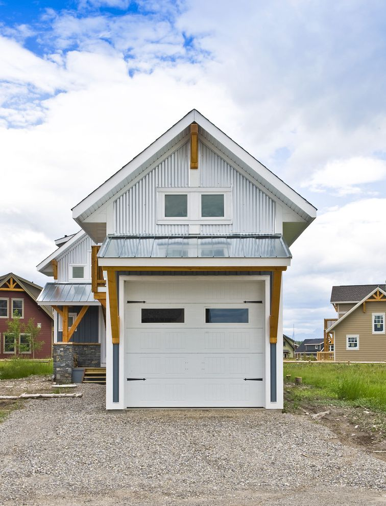 Metal Garage with Apartment with Eclectic Garage Also Dark Gray Siding Gravel Driveway Metal Roof Metal Siding Mixed Exterior Mixed Material Exterior Stone Exterior White Garage Door White Trim Wood Beams Wood Outdoor Stairs Wood Patio Wood Timbers