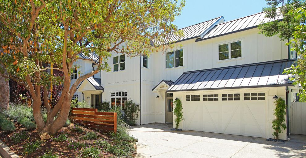 Metal Garage with Apartment with Traditional Garage Also Bark Mulch Board and Batten Siding Climbing Vines Covered Entry Driveway Gable Roof Garage Doors Metal Roof Tree Two Story White Cladding Wood Slat Fence