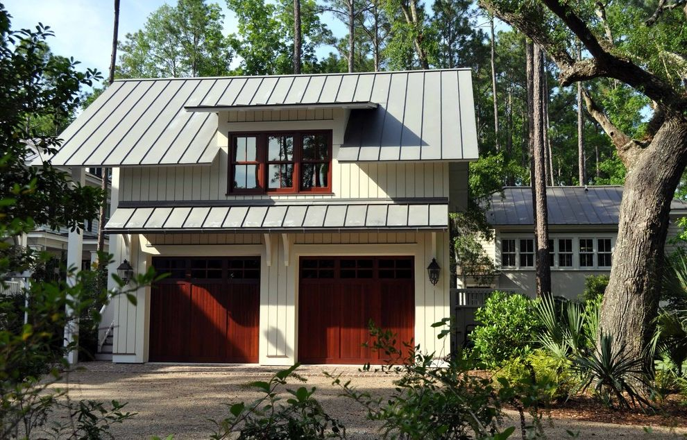 Metal Garage with Apartment with Traditional Garage  and Dormer Windows Garage Garage Door Gravel Driveway Metal Roof Outdoor Lighting Overhang Sconce Wall Lighting White Trim White Wood Wood Column Wood Post Wood Siding