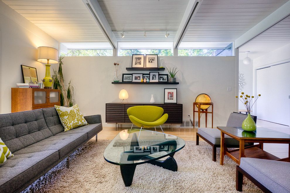 Raymond Furniture Store with Midcentury Living Room Also Exposed Beams Floating Shelves Glass Coffee Table Green Accent Chair Houseplants Midcentury Midcentury Modern Modern Icons Sloped Ceiling Tufted Sofa Wall Shelves Wood Ceiling Wood Flooring
