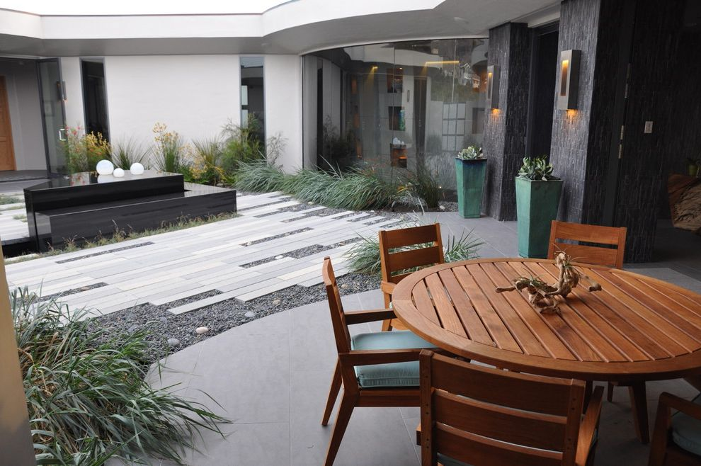 Rectangular Pavers   Contemporary Landscape  and Black Concrete Courtyard Glass Panels Gravel Gray Green Plant Pots Outdoor Dining Pavers Round Dining Table Seat Cushions Stones Tall Grasses Teak Tile Walls Water Feature White