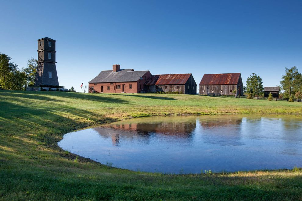 Restore Newington Nh with Farmhouse Exterior  and Cow Pond Farmhouse Landscape Gable Roof Grass Outbuildings Rusted Metal Roof Rustic Landscape Rustic Wood Siding Saltbox Roof Separate Structures Tower Weathered Wood Siding