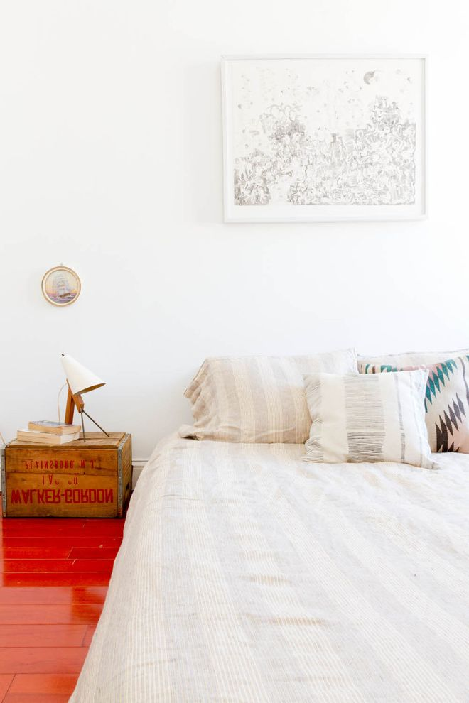Shipping Crate Homes with Eclectic Bedroom  and Bed Pillows Bedside Table Glossy Floor Loft Neutral Colors Nightstand Reading Lamp Red Accent Red Floor Striped Bedding Vintage Crate Wall Art Wall Decor Wood Flooring