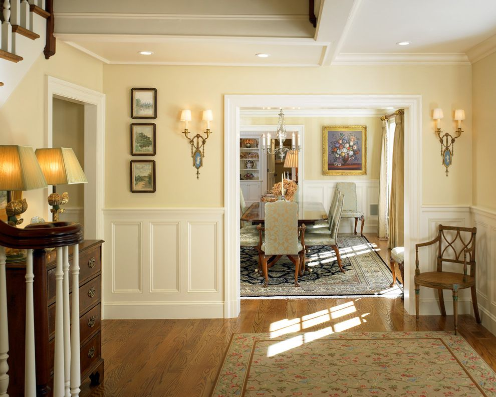 What is Wainscoting   Traditional Entry Also Cream Walls Dining Room Entryway Floral Rug Formal Entry Hardwood Floor Recessed Lighting Stairs Wainscoting Wall Sconces White Door Trim Wood Chair