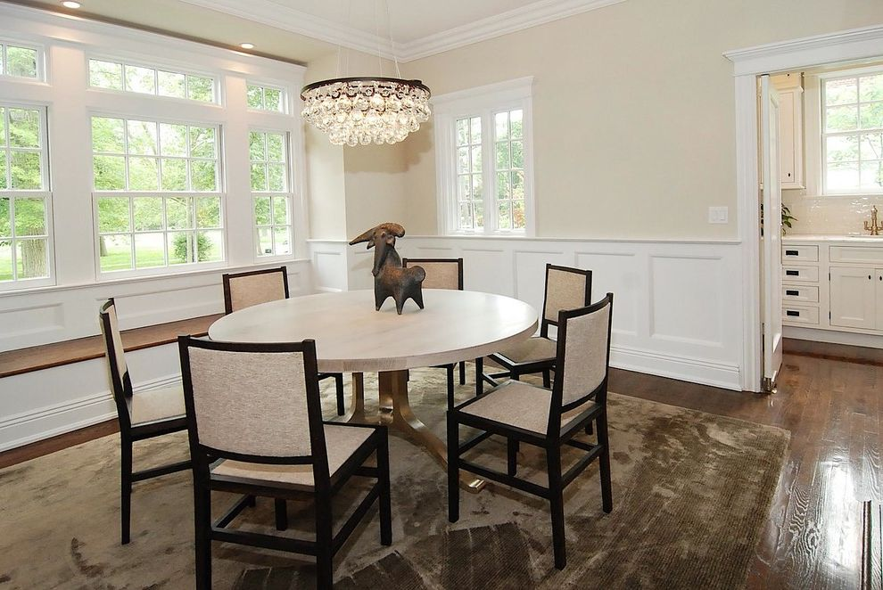 What is Wainscoting with Eclectic Dining Room Also Area Rug Beige Chandelier Dark Stained Wood Frame and Panel Woodwork Round Dining Table Transom Windows Wainscot White Painted Wood Wood Floor