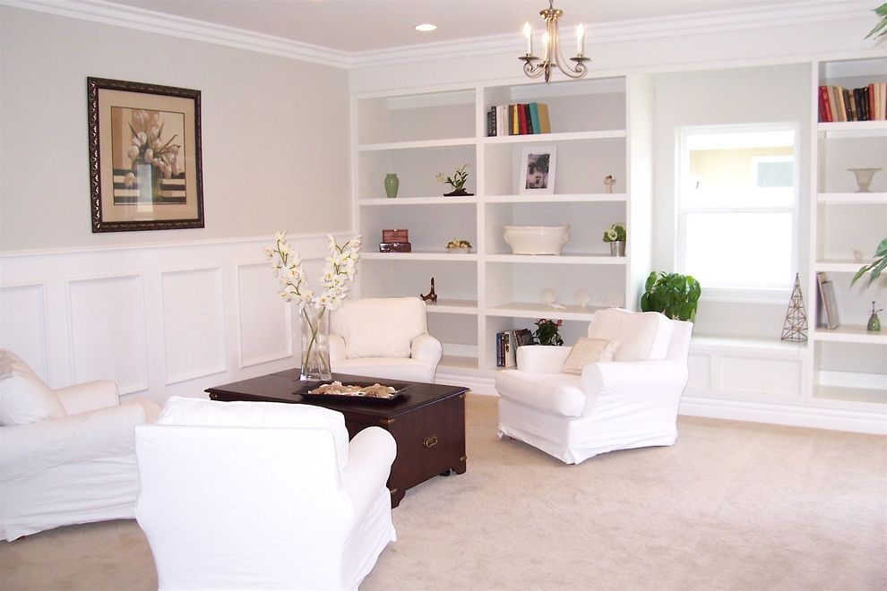 What is Wainscoting with Traditional Living Room Also Bookcase Bookshelves Built in Shelves Ceiling Lighting Chandelier Crown Molding Floral Arrangement Monochromatic Neutral Colors Recessed Lighting Slipcovers Wainscoting White Wood Wood Trim