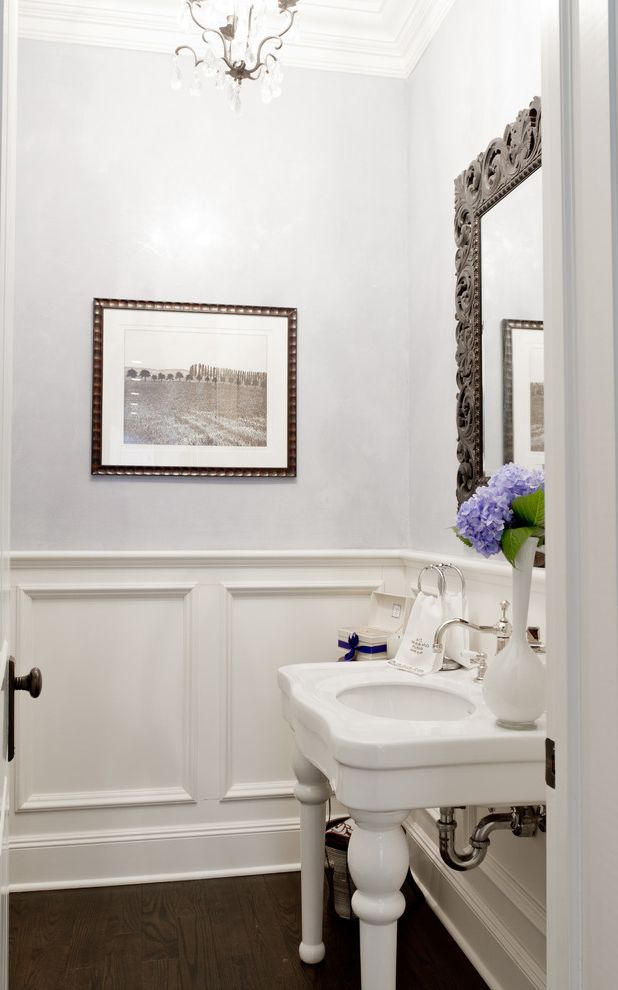 What is Wainscoting with Traditional Powder Room  and Hydrangeas Lever Faucet Light Gray Walls Open Sink Ornate Mirror Frame Purple Flowers Recessed Panel Wainscoting Small Bathroom Turned Legs Undermount Sink Wainscoting White Sink White Vase