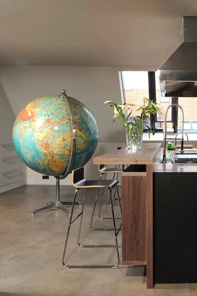 World Globes for Sale with Eclectic Kitchen  and Built in Drawers Concrete Floor Counter Stools Dark Stained Wood Globe Hood Kitchen Island Stainless Steel Vaulted Ceiling White Walls