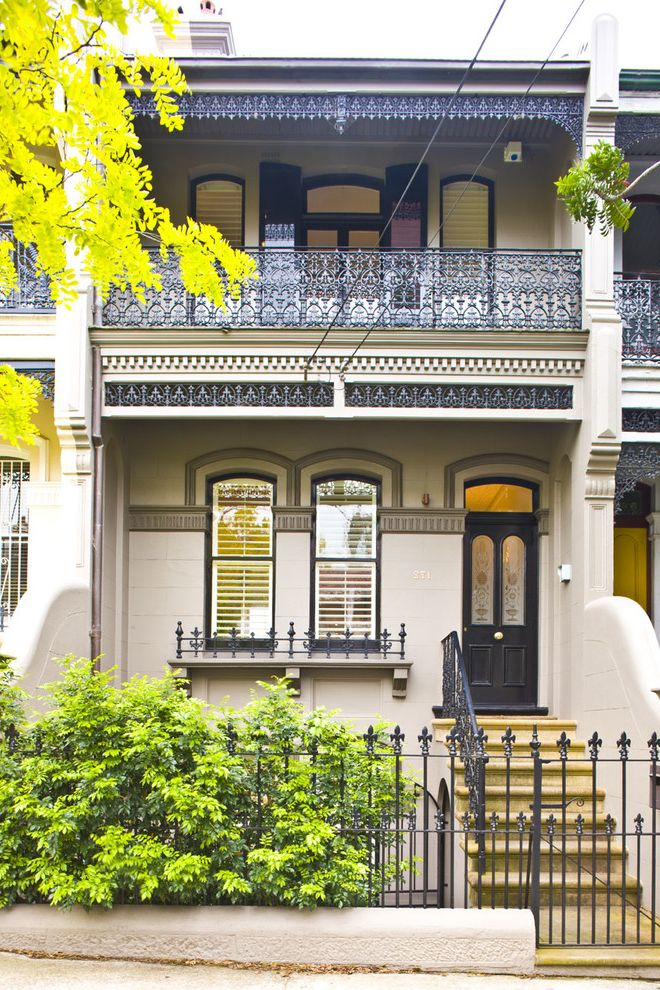 Chart House Philadelphia with Traditional Exterior  and Arched Windows Balcony Black Door Black Metal Railing Corbels Filagree Fleur De Lis Front Door Front Steps Handrail Intricate Railing Row House Window Panels Wrought Iron Railing