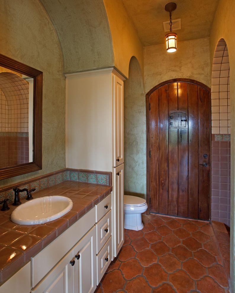 Closet in Spanish   Mediterranean Bathroom Also Arches Bathroom Mirror Blue Wall Glazed Ceramic Tile Pattern Tile Pendant Light Terra Cotta Tile Floor Undermount Sink White Cabinets Wood Door