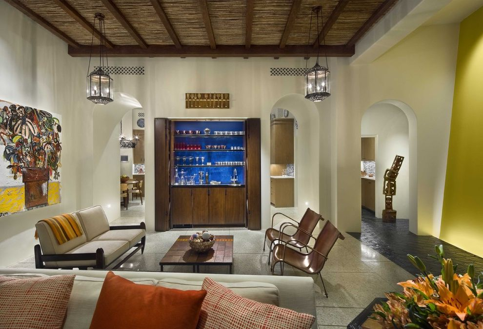 Closet in Spanish   Tropical Living Room  and Archway Artwork Bar Area Barware Dark Floor Exposed Beams Lanterns Leather Armchair Neutral Colors Wall Art Wall Decor