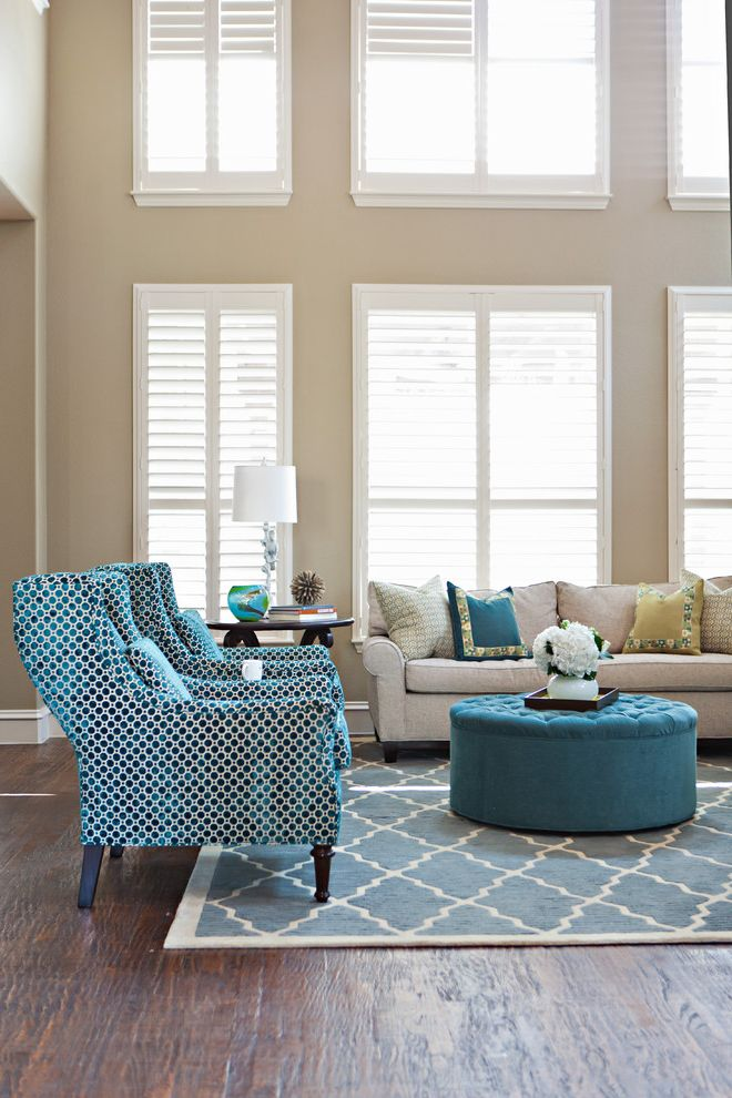 Furniture Stores Madison Wi with Transitional Living Room  and Area Rug Beige Walls Blinds Blue Pillows Printed Fabric Round Ottoman Seating Area Side Table Sofa Table Lamp Tufted Upholstery White Trim