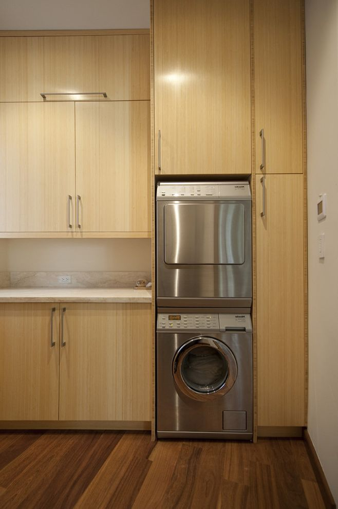 Ge Stackable Washer Dryer   Contemporary Laundry Room Also Blonde Wood Built in Storage Front Load Washer and Dryer Neutral Colors Stackable Washer and Dryer Stacked Washer and Dryer Wood Cabinets Wood Flooring