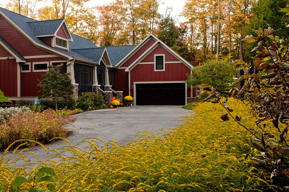 Houses in Sioux Falls with Craftsman Landscape  and Barn Craftsman Dormers Driveway Entrance Entry Flowering Plants Foundation Planting Garage Door Mass Planting Red House Red Siding Yellow Flowers
