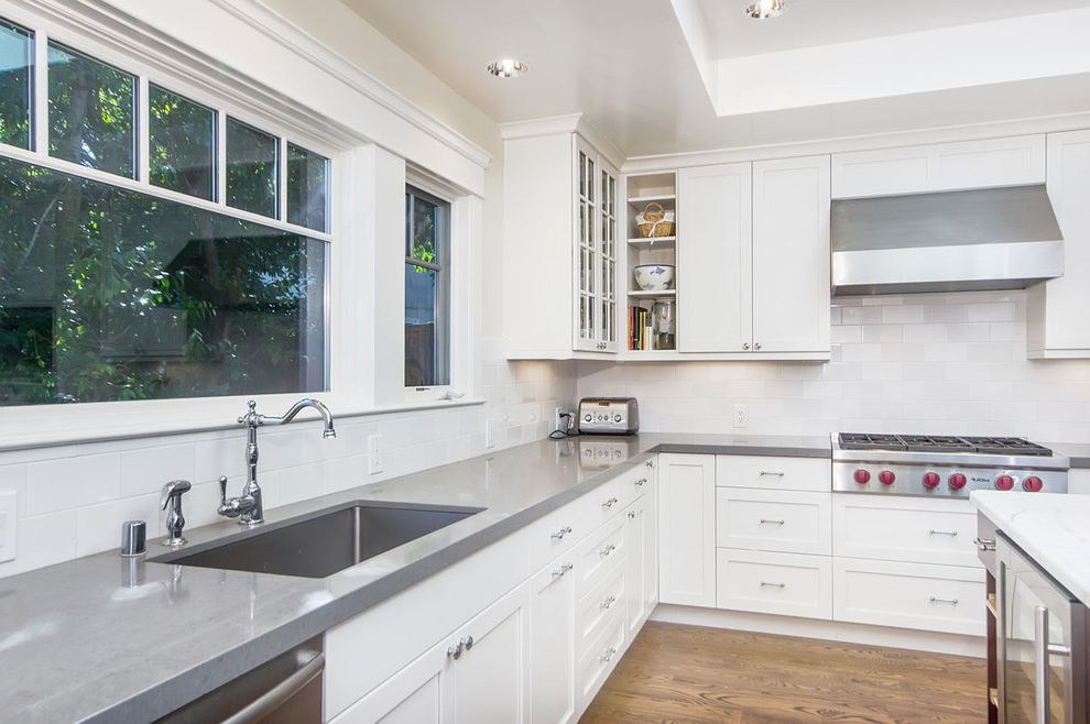 How to Clean Quartz Countertops with Craftsman Kitchen  and Beverage Cooler Glass Front Cabinets Gray Counters Hood Kitchen Island Recessed Lights Stainless Steel Appliances Tile Backsplash Tray Ceiling White Cabinets Wood Floor