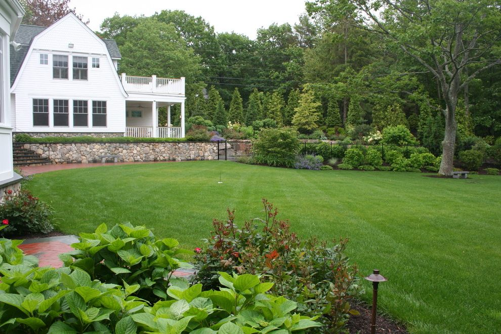 Landscape Companies Near Me   Traditional Landscape  and Brick Paving Cottage Garden Covered Porch Deck Dutch Colonial Gambrel Roof Garden Lighting Grass Handrail Lawn Outdoor Lighting Path Planters Stone Wall Turf Walkway Wood Railing Wood Siding