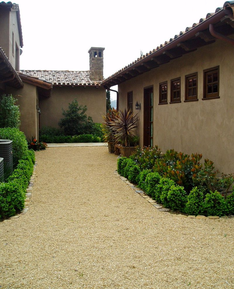 Pioneer Sand and Gravel with Mediterranean Landscape  and Gravel Hedge Potted Plants Small Exterior Lantern Stone Chimney Stones Tan Tile Roof Tuscan