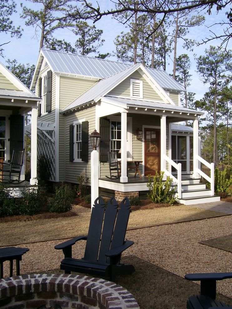 Rent1sale1   Farmhouse Exterior  and Adirondack Chairs Black Shutters Covered Porch Exposed Rafters Firepits Front Porch Gable Vent Gravel Lap Siding Lattice Metal Roof Rocking Chair Steps Trellis White Banister White Columns White Trim Windows
