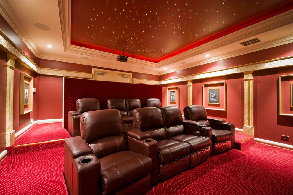 Royal Palm Theater   Traditional Home Theater  and Fluted Pilasters Framed Artwork Lighted Ceiling Luxury Movie Theatre Ornate Crown Molding Recliner Chairs Red Carpet Red Walls Tray Ceiling