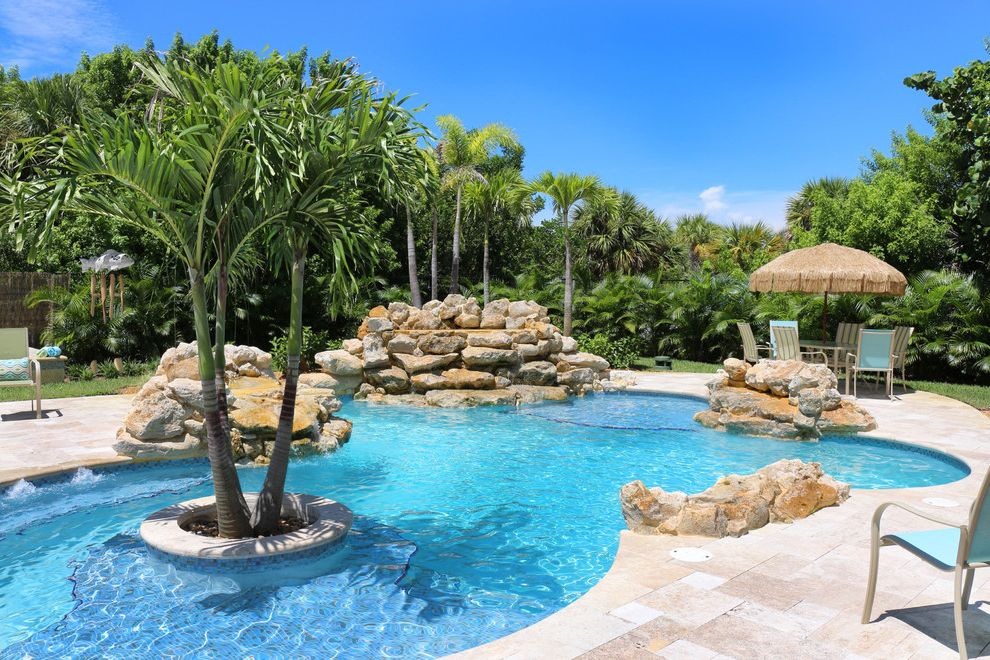 Royal Palm Theater with Tropical Pool  and Beach Boulders Contemporary Curved Pool Eclectic Florida Grass Umbrella Green Antiques Ocean View Palm Trees Stone Tropical Vero Beach