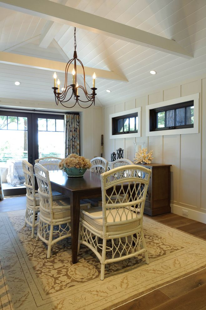 Sherwin Williams Austin with Beach Style Dining Room Also Area Rug Board and Batten Chandelier Coastal Exposed Beams Neutral Colors Sloped Ceiling Vaulted Ceiling Wicker Dining Chairs Wood Paneling