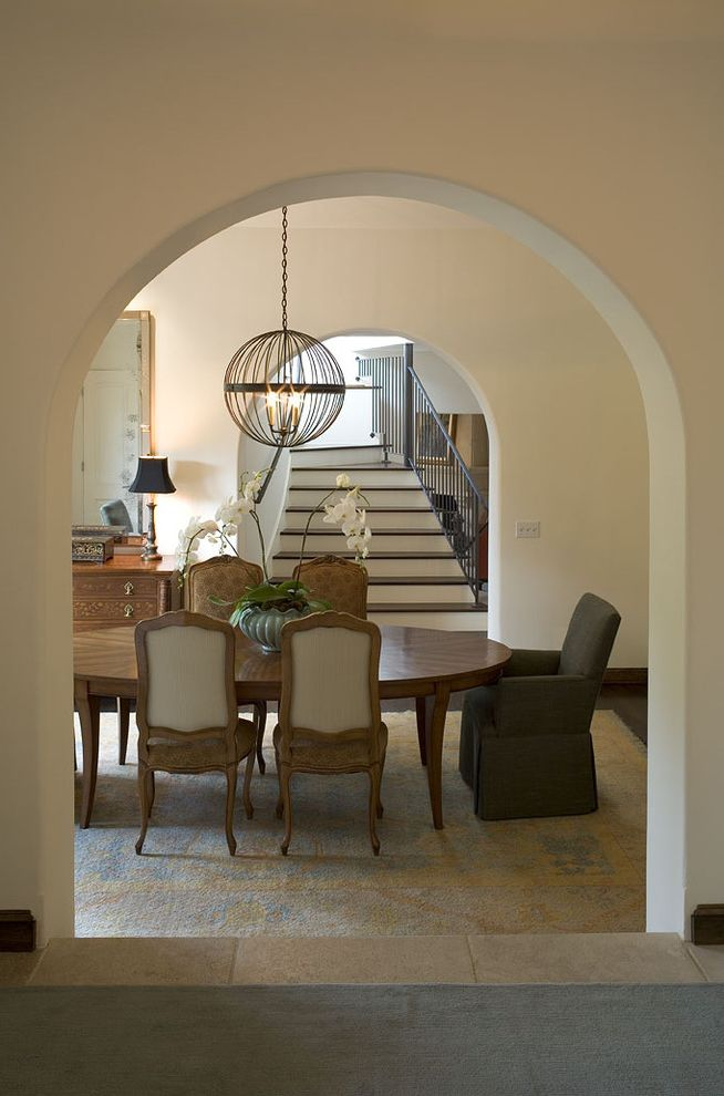 Sherwin Williams Denver   Traditional Dining Room  and Arched Doorway Area Rug Dining Area Louis Chairs Neutrals Orb Oval Table Pendant Light Staircase Stone Tile Floor Upholstered Chair