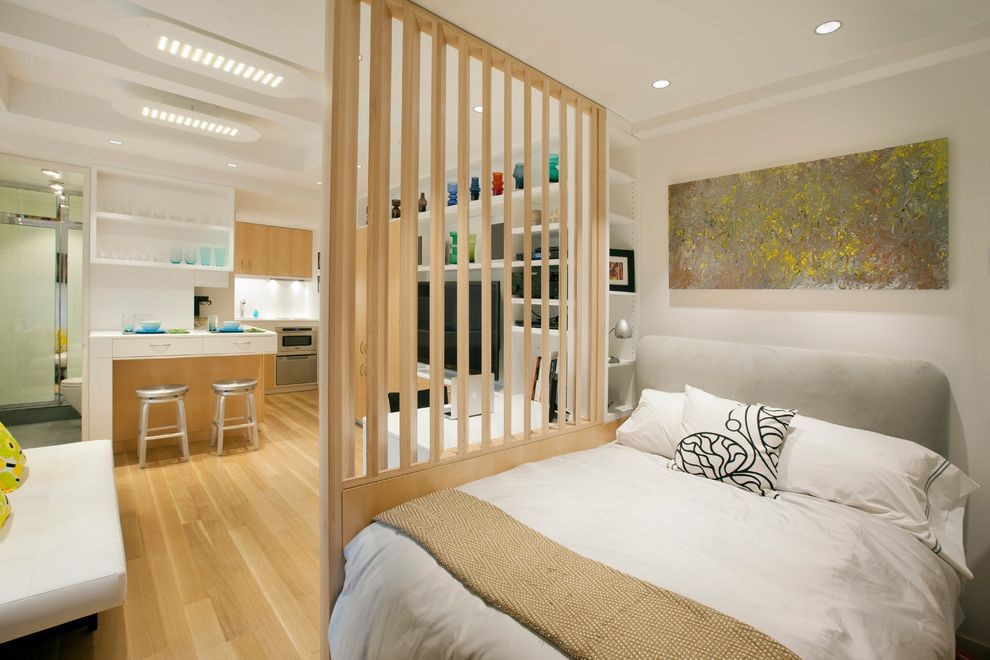 Signature Place Apartments   Scandinavian Bedroom Also Apartment Bed Pillows Bedding Family Room Kitchenette Light Wood Floors Living Room Micro New York City Open Concept Recessed Lighting Screen Small Studio Apartment Upholstered Headboard Wall Art