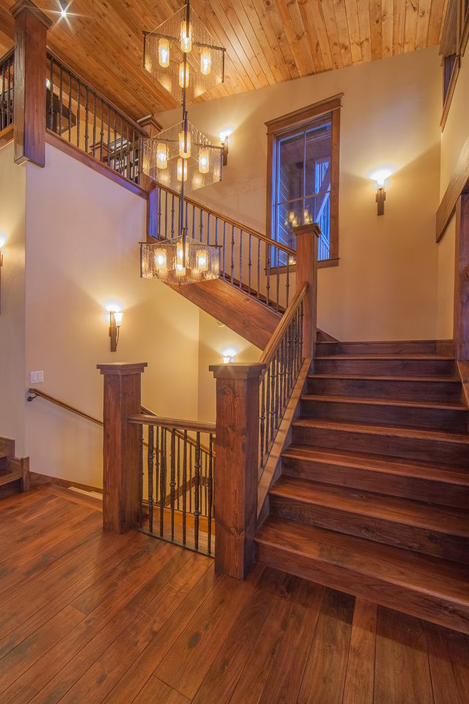 Staircase in the Woods with Rustic Staircase Also Beige Wall Curved Staircase Metal Railing Oversized Chandelier Tiered Chandelier Wall Sconce Wood Ceiling Wood Floor Wood Staircase Wood Stairs Wood Window Trim